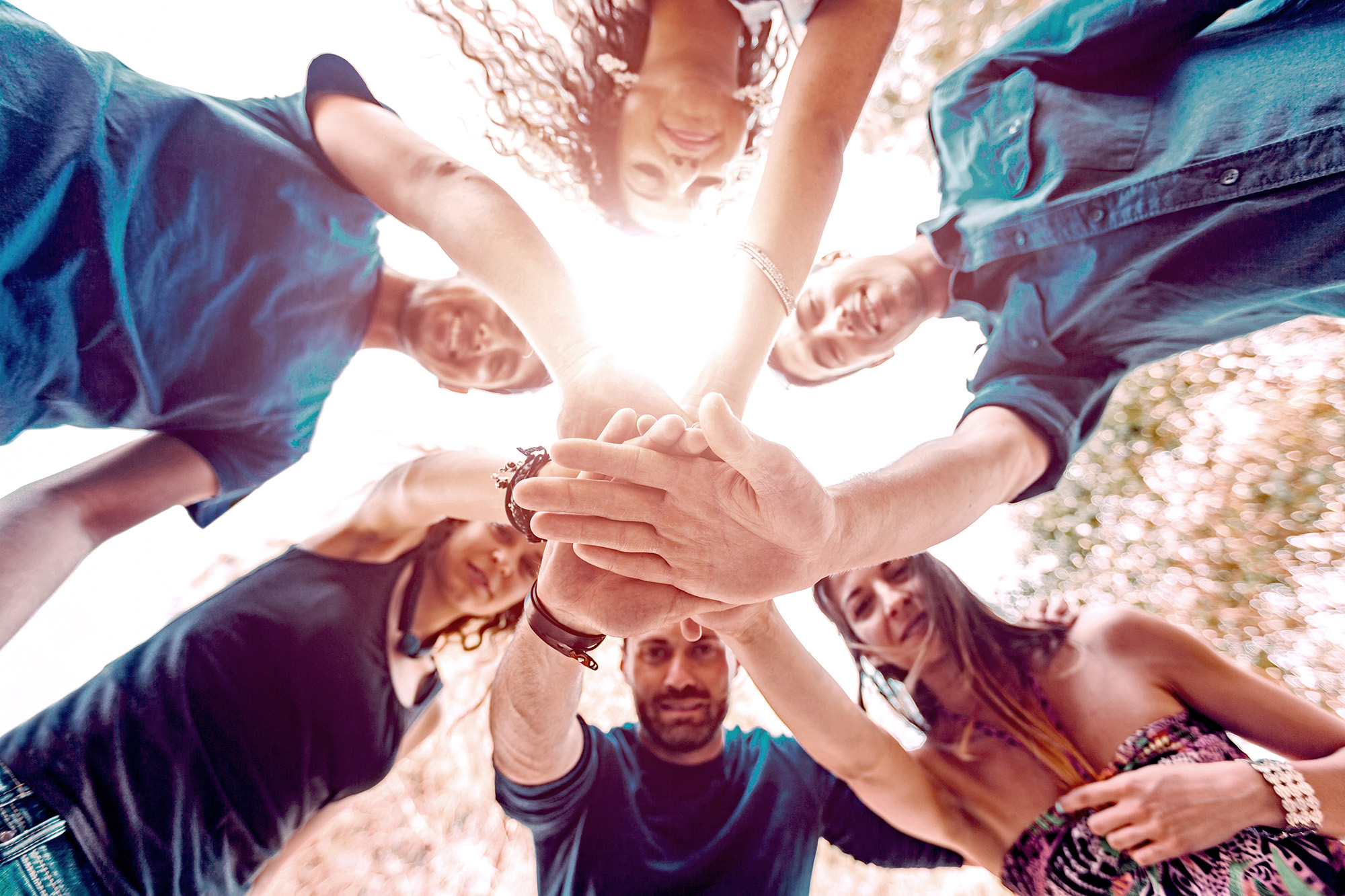 Multiracial group of friends with hands on stack and looking down at camera. They are six persons, three boys and three girls, on their early twenties. Teamwork and cooperation concepts.