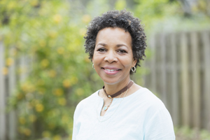Portrait of a mature African-American woman in her 50s standing outdoors in the back yard by a fence. She is smiling at the camera.