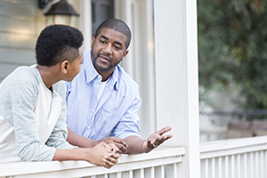 A father talks with his hands as he leans against the railing of his front porch with his preteen son and has a serious discussion.