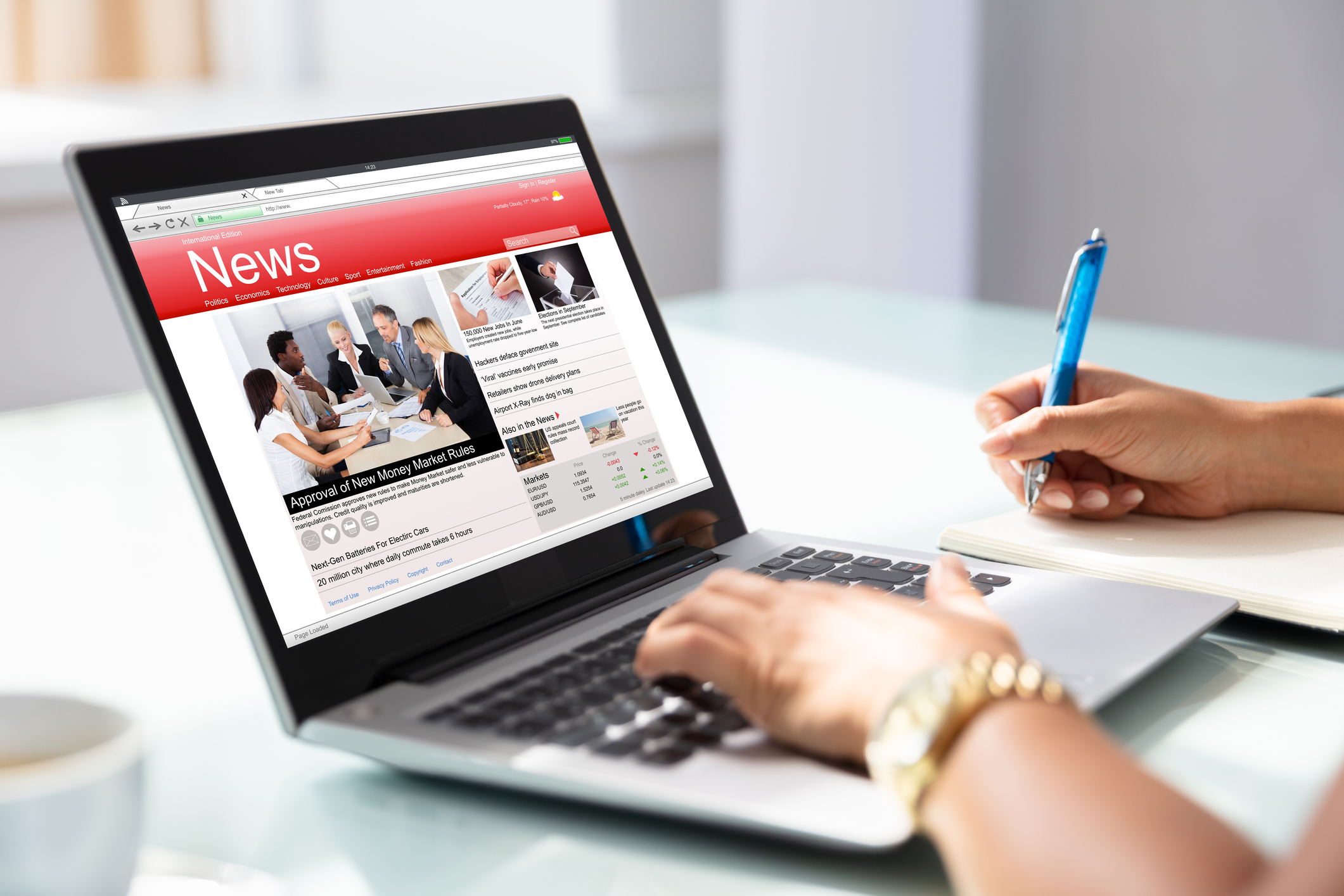 Close-up Of Businesswoman's Hand Checking Online News On Laptop In Office