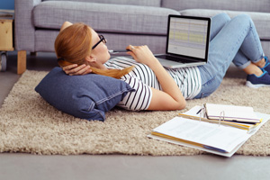 Young woman relaxing at home working or studying on a laptop computer lying on a rug on the floor with a notebook and binder alongside her, side view from behind