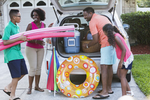 An African American family of four packing their car for a trip to the beach or pool, with cooler, umbrella and toys.  The teenage boy is carrying pool noodles and the 10 year old girl is watching the father put a picnic basket into the car.