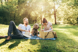 father and daughter spending time together, lying on a blanket in a park
