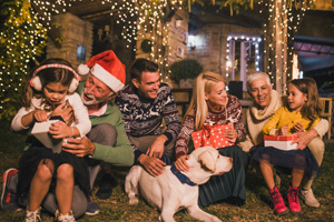 Joyful family holding Christmas presents and petting a dog in front of a decorated house
