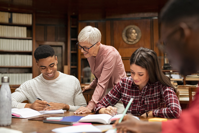 Senior teacher helping young african man at the library with friends. Group of university guys and girl sitting at desk while mature professor helping them in reading hall. Group of multiethnic high school students studying with lecturer.