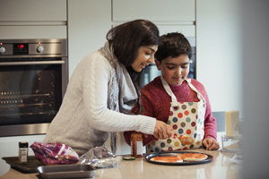 A mother is helping her autistic son spread the tomato sauce over the pizza dough in preparation for dinner.