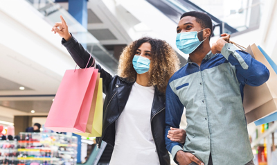 Shopping during quarantine concept. Young african american couple doing shopping together in city mall, wearing protective face masks, panorama. Black lady showing her boyfriend new store, copy space