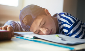 Photo of bored boy sleeping on the books
