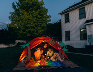 A dad with his two sons camp out in the backyard of their home due to the coronavirus restrictions and quarantine. They have pitched a tent and created a beach scene with stuffed animal friends and have a fake campfire. They are making the best of their situation and long to return to the real outdoors.