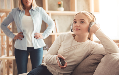 Beautiful woman is scolding her teenage daughter, girl is listening to music in headphones and ignoring her mom