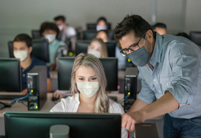Teacher wearing a facemask and helping female student at an IT class - education during the COVID-19 pandemic